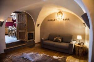 Ampia sala con camino, divano letto e accesso alla cucina con volte a botte- Casa per vacanze a Pragelato
